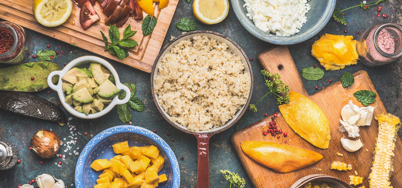 Quinoa salad preparation with vegetables and fruits cooking ingredients on dark rustic background, top view. Superfood, healthy Eating or vegan food concept