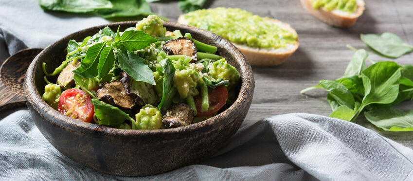 Spinach salad with avocado in the wooden bowl. Superfood. Fitness food.