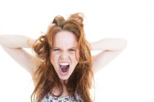 Entzugserscheinungen von Nikotin - wütende Frau greift sich in die Haare